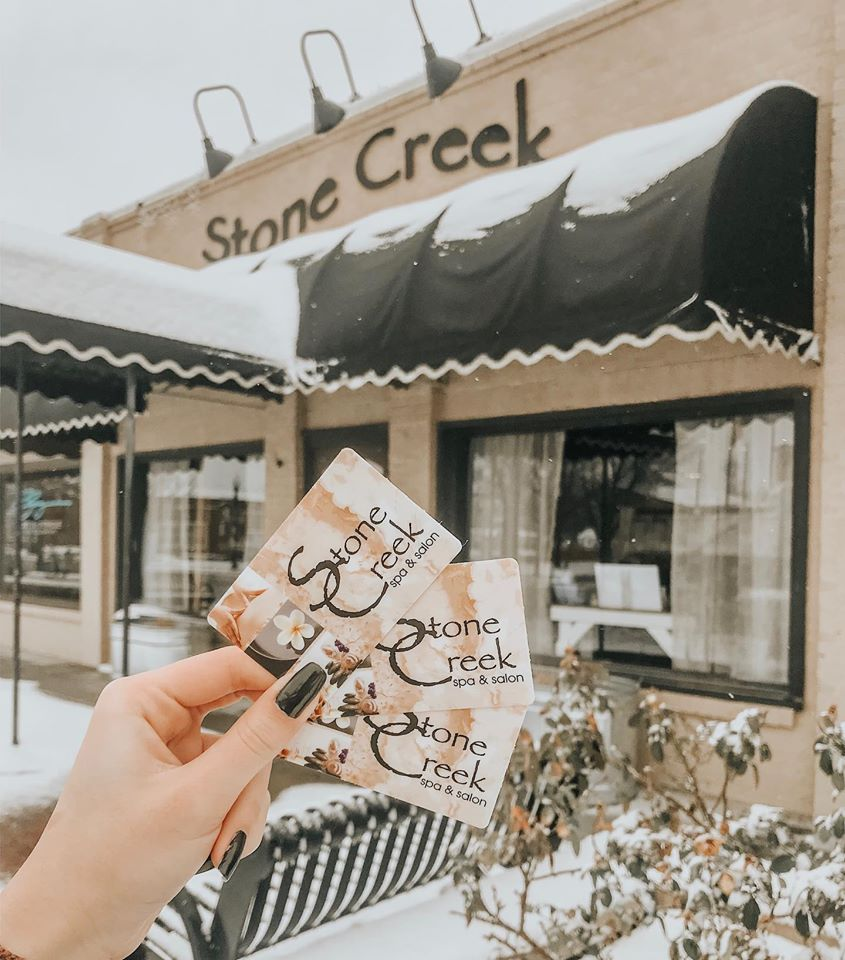 picture of gift card being held in front of the store